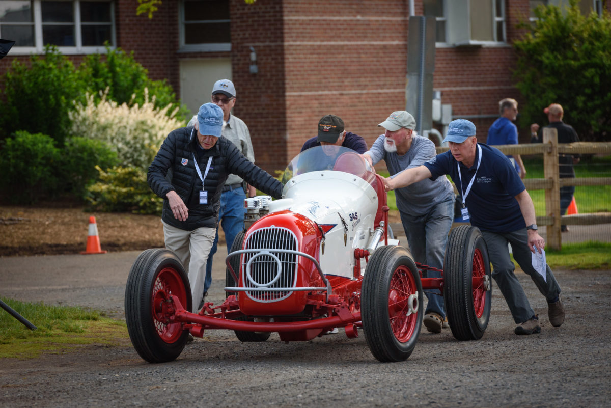 five men in baseball caps pushing red race car down dirt road at Greenwich Concours